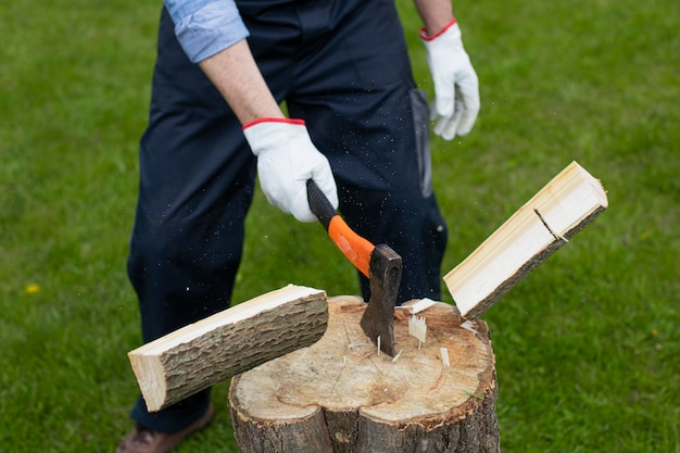 Adult man is chopping wood with axe Premium Photo