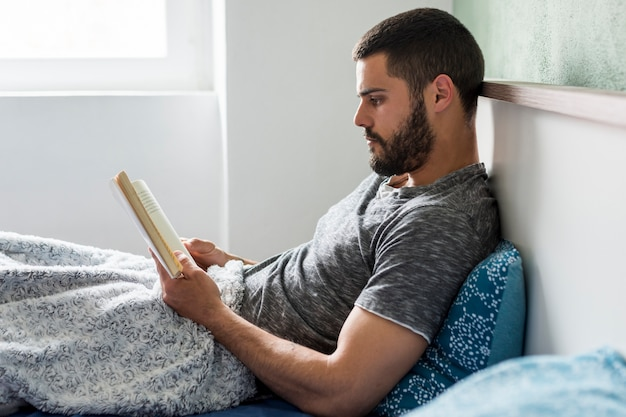 Adult man lying in bed and reading Free Photo