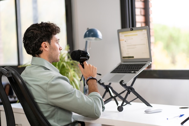 Adult man records a podcast from home, digital home work concept, young entrepreneur Premium Photo