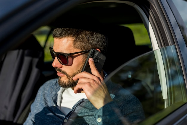 Adult man sitting in car and talking on phone Free Photo