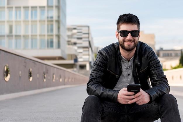 Uomo adulto che si siede sullo smartphone di terra della tenuta Foto Gratuite