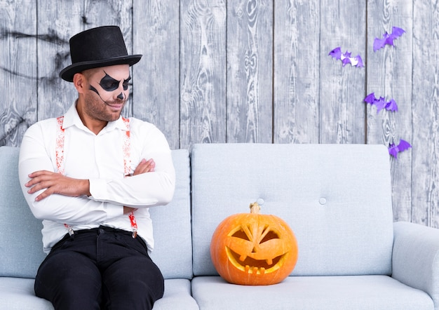 Adult man staring at halloween pumpkin Free Photo