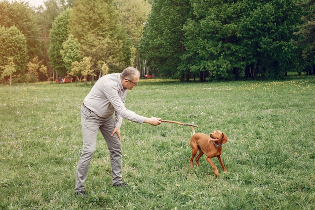 Adult man in a summer park with a dog Free Photo