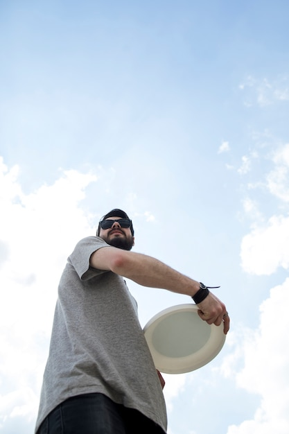 Adult man in sunglasses holding frisbee disc Free Photo