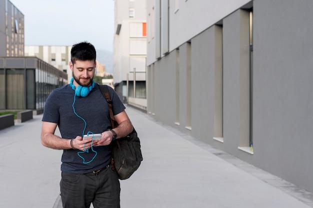 タブレットとヘッドフォンで歩く大人の男 無料写真