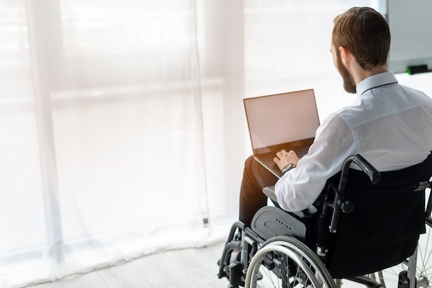 Adult man in wheelchair working on a laptop Free Photo