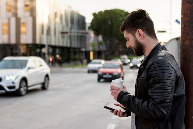 Adult man with coffee using mobile phone Free Photo