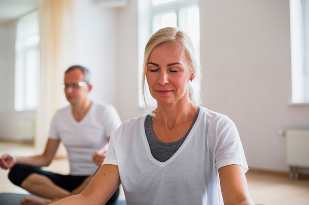 Adult man and woman practicing yoga Free Photo
