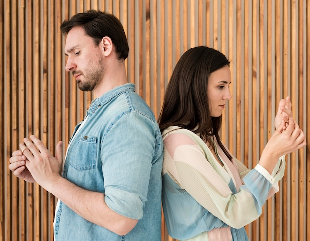 Adult man and woman taking wedding rings off Free Photo