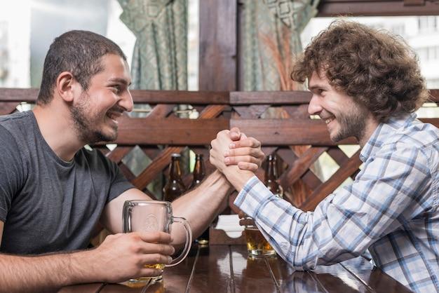 Adult men arm wrestling in pub Free Photo