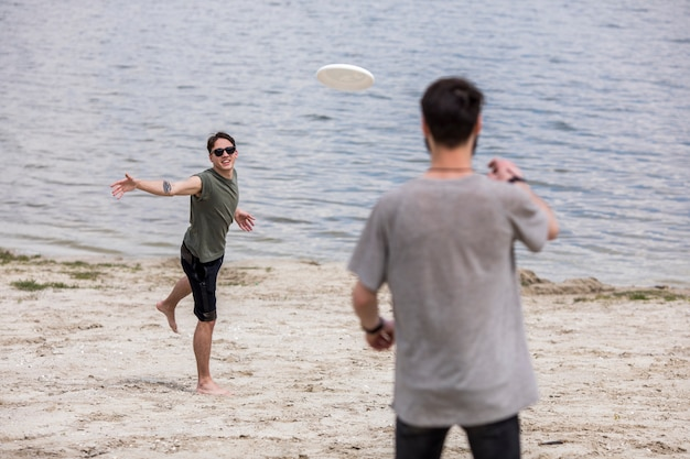 Adult men playing frisbee on shore during holidays Free Photo