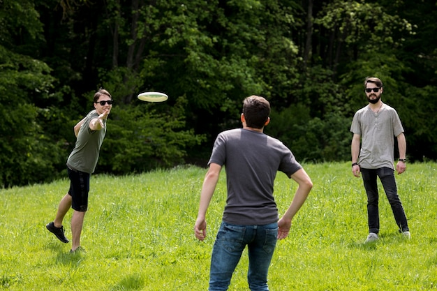 Adult men resting in park by playing frisbee Free Photo