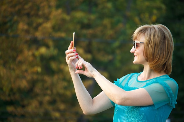 Adult middle-aged business woman on the street makes selfie on a smartphone. Premium Photo