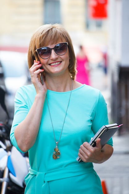 Adult middle-aged business woman with documents in her hands walking down the street and talking on a smartphone Premium Photo