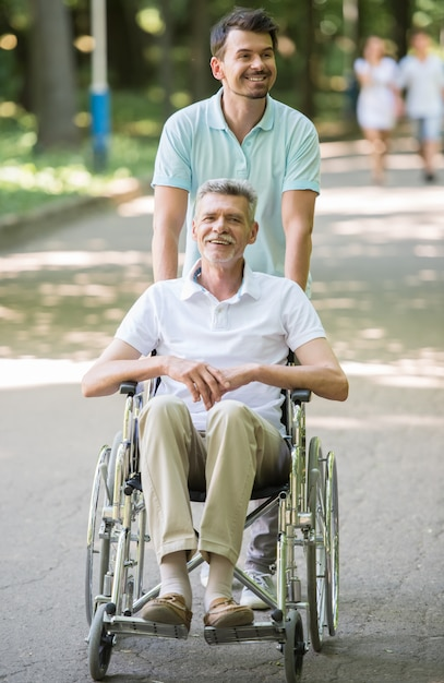Adult son walking with disabled father in wheelchair outdoor Premium Photo