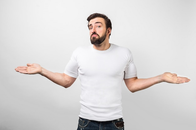An adult standing near white wall with a sad face and showing that he have nothing with his right now or he doesn't know anything. he is looking straight forward. isolated on white wall. Premium Photo
