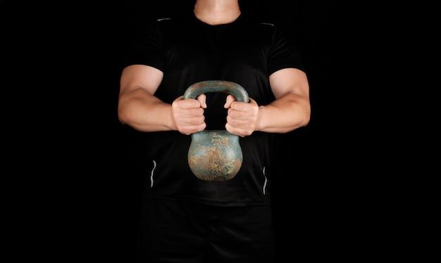 鉄のケトルベルを保持している黒い服を着た大人の強い選手 Premium写真