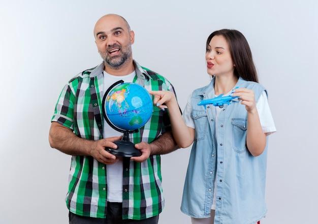 大人の旅行者のカップルは、地球儀をまっすぐに見ている男性に感銘を与え、模型飛行機を持って地球儀を見てそれに触れて喜んでいる女性 無料写真