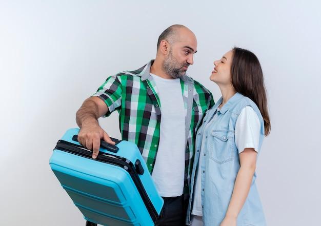 La coppia di viaggiatori adulti ha soddisfatto l'uomo che tiene la valigia e la donna sorridente che si guardano l'un l'altro Foto Gratuite