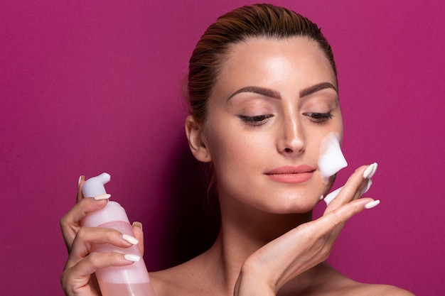 Adult woman applying moisturizer on her face Free Photo