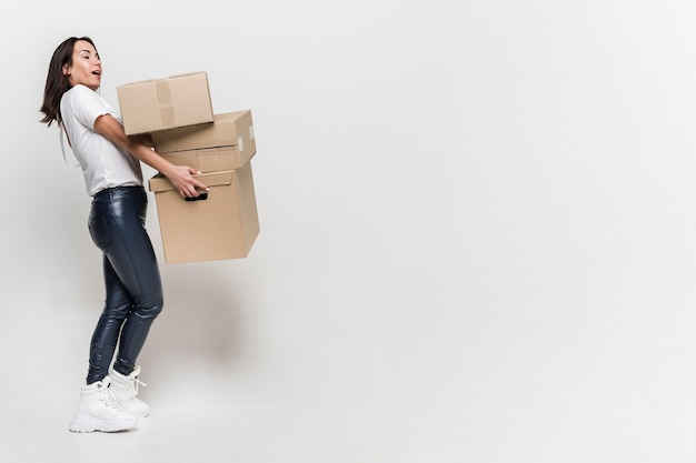 Adult woman carrying cardboard boxes with copy space Free Photo