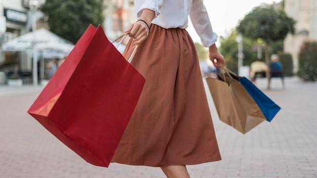 カラフルな買い物袋を運ぶ大人の女性 無料写真