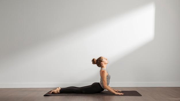 Donna adulta che fa yoga a casa Foto Gratuite