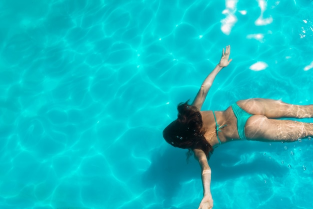 Adult woman floating under bright pool water Free Photo