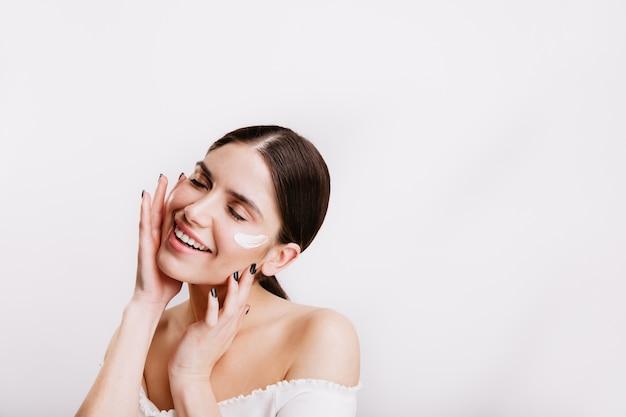Взрослая женщина в белом топе ухаживает за кожей лица, нанося крем. портрет девушки с хвостиком на изолированной стене. Бесплатные Фотографии