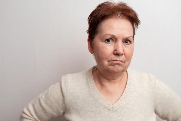 Взрослая женщина на белом в легкий свитер. Premium Фотографии