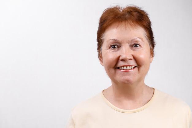 Взрослая женщина на белом в легкой футболке Premium Фотографии