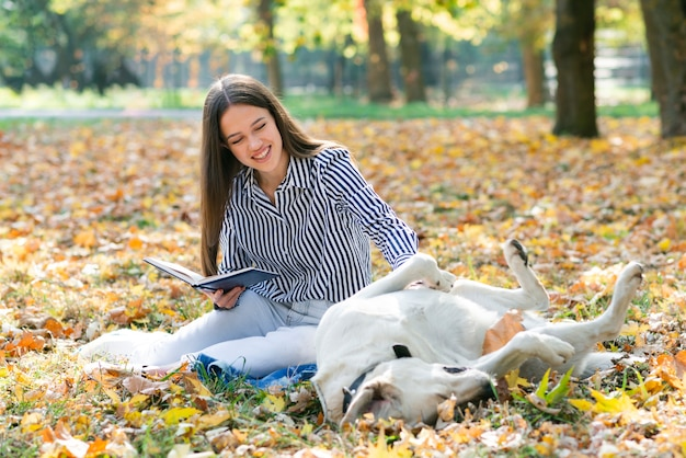 Adult woman petting her dog in the park Free Photo