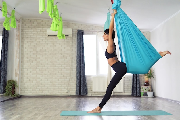 Adult woman practices anti-gravity yoga Free Photo