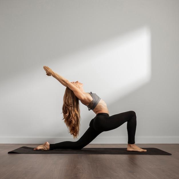 Взрослая женщина, практикующая йогу дома Бесплатные Фотографии