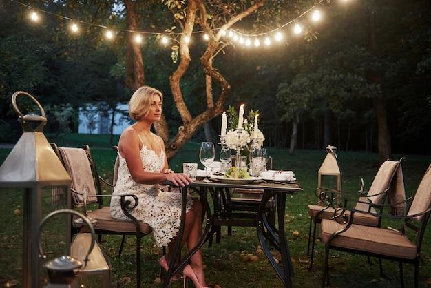 大人の女性がレストランの屋外部分でキャンドルとワイングラスが付いている椅子に座っています。 無料写真