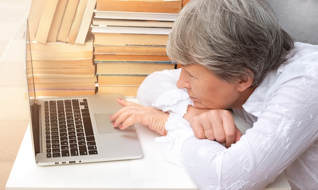 An adult woman sits at a table with a laptop by stacks of books. Premium Photo