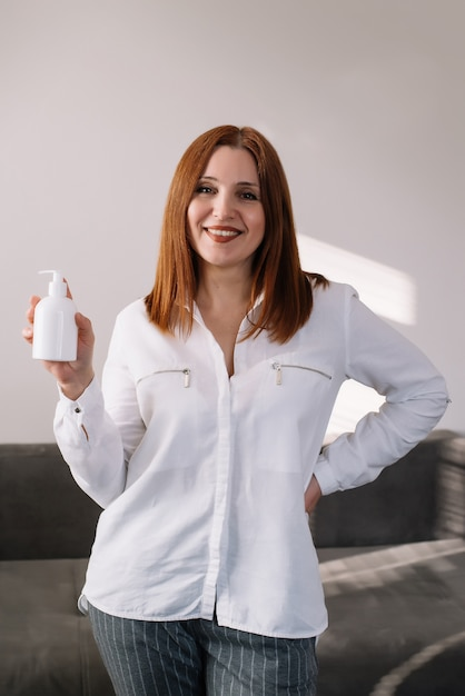 Adult woman smilling and holding sanitizer gel Premium Photo