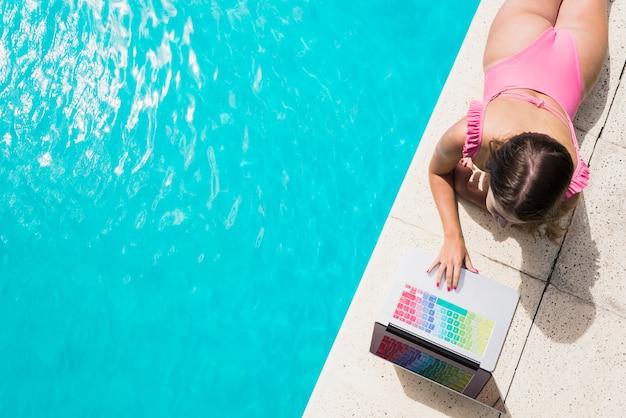 Adult woman using laptop near swimming pool Free Photo