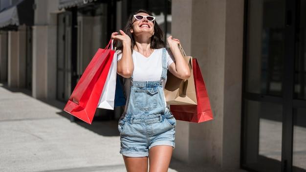 買い物袋と一緒に歩いている大人の女性 Premium写真