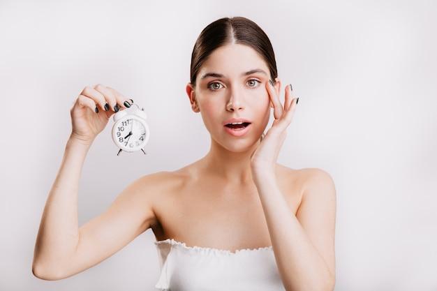 Donna adulta con pelle sana elastica, che tiene piccola sveglia bianca. Foto Gratuite