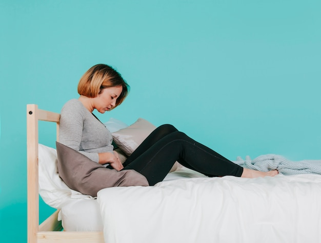 Adult woman with hurting stomach on bed Free Photo