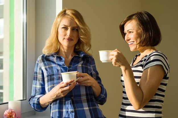 Adult women drink coffee talk laugh Premium Photo