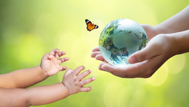 Adults are sending the world to babies. concept day earth save the world save environment. the world is in the grass Premium Photo