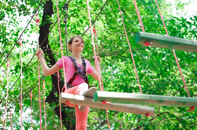 Adventure climbing high wire park - hiking in the rope park girl Premium Photo