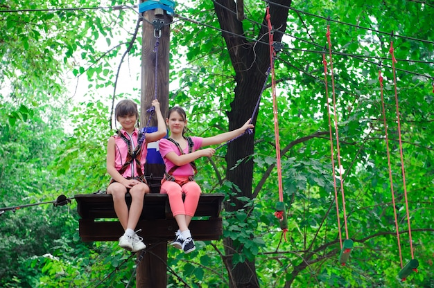 Adventure climbing high wire park - hiking in rope park two girls Premium Photo