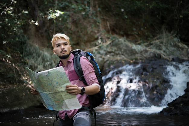 Adventure man observing map on a mountain path  to find the the right way. Free Photo