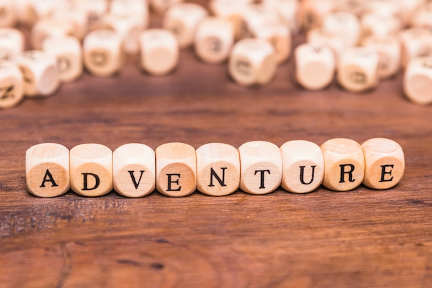 Adventure text arranged with wooden cubes Free Photo