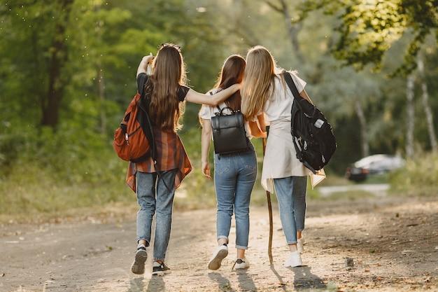 Avventura, viaggi, turismo, escursione e concetto di persone. tre ragazze in una foresta. Foto Gratuite