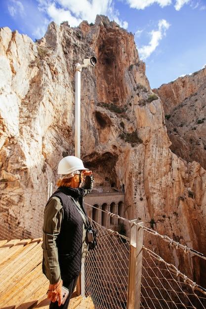 山探検での休暇中に崖を鑑賞するヘルメットを持つ冒険的な女性 Premium写真