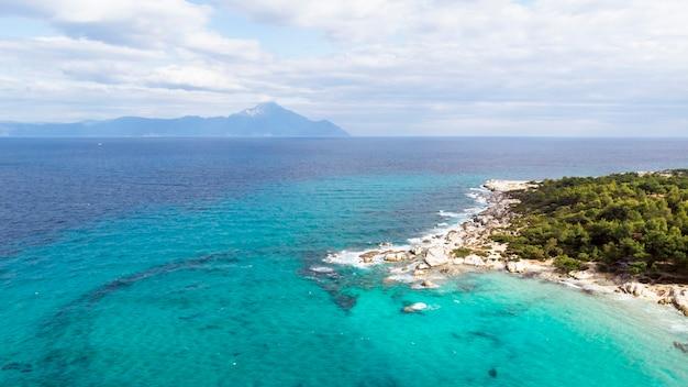 Побережье эгейского моря с голубой прозрачной водой, зеленью вокруг, скалами, кустами и деревьями, вид с дрона, греция Бесплатные Фотографии